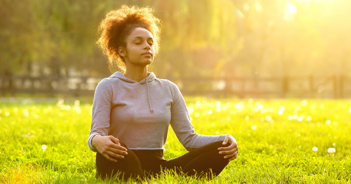 Woman is outside meditating in an open field
