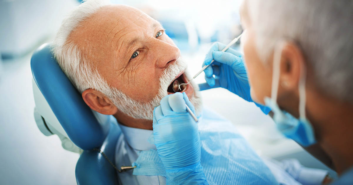 Dentist examining a senior male patient