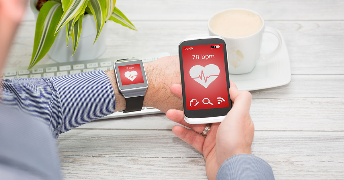 Man using smartphone and smartwatch to measure heart rate