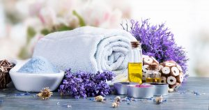 Towel, lavender bushes and essential oil