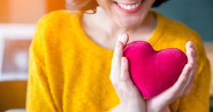 Woman hands in yellow sweater holding pink heart