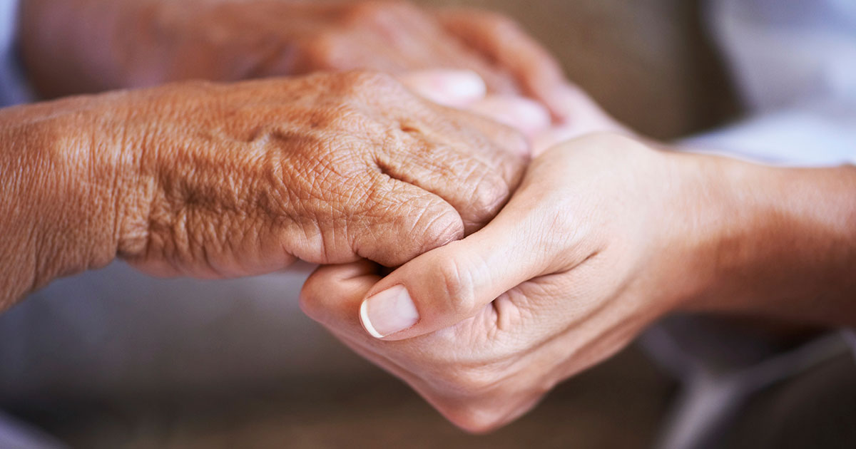 Caregiver holding patient's hands