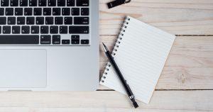 Small journal beside a laptop