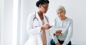 A female doctor standing next to female patient and showing her something on digital tablet