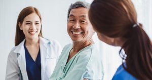 Doctor and nurse reassure older male patient