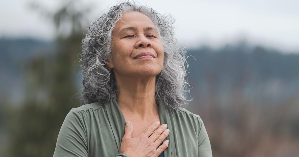 Older woman doing breathing exercises outside