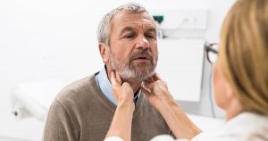 Female doctor doing throat examination on older man
