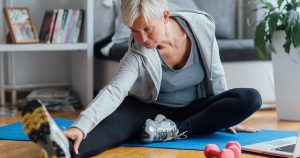 Mature woman doing some stretches at home