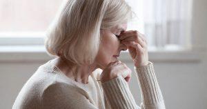 Fatigued upset older woman massaging nose bridge