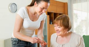 Caregiver helping older female patient at home