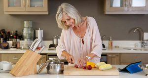 Woman in kitchen cutting healthy fresh vegetables