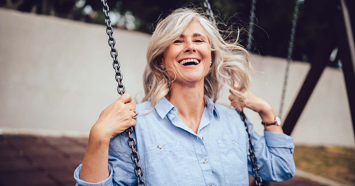Mature woman with gray hair sitting on swing