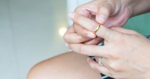 Woman is taking ring off her swollen finger