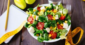 Healthy salad, body measuring tape, food log and other weight management tools