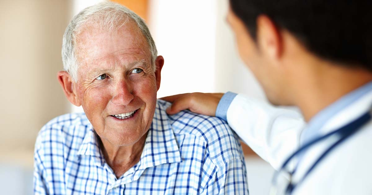 Doctor comforting senior male patient