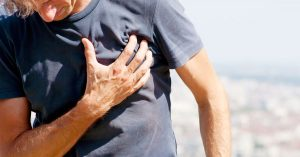 Man is clutching his chest due to chest discomfort or pain