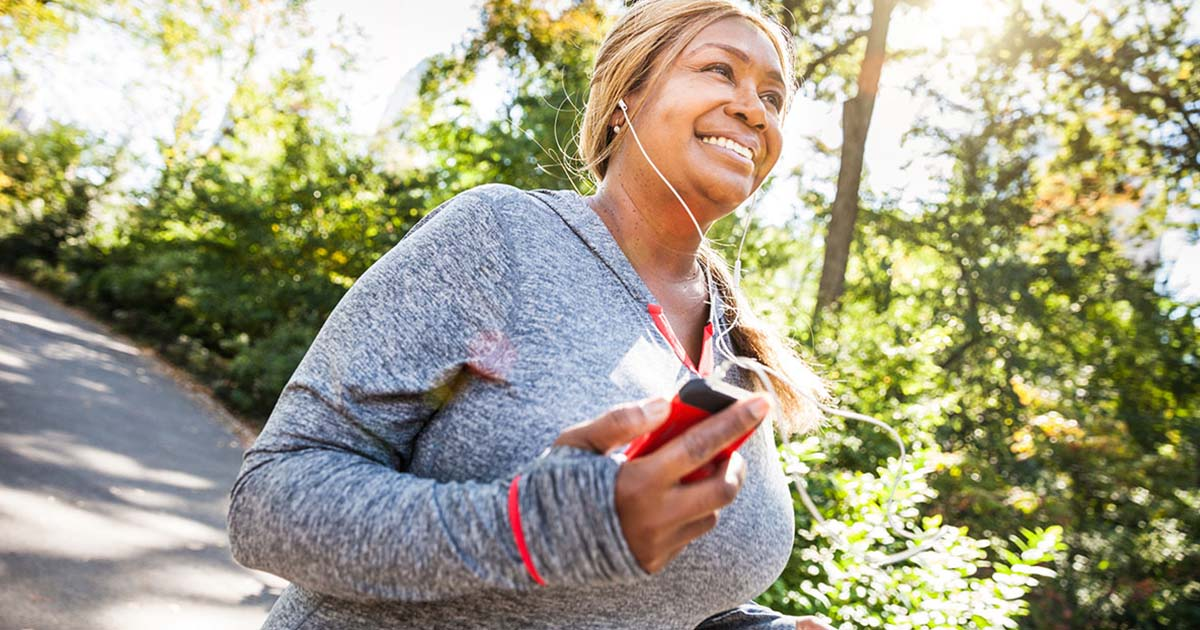 Woman outside running while listening to music