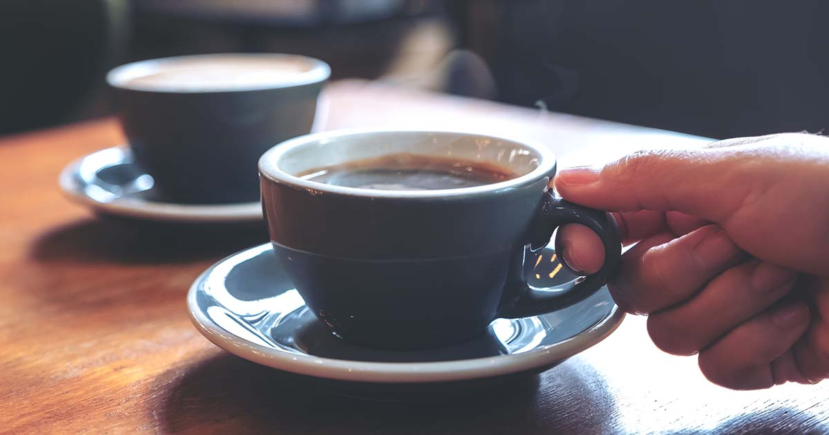 Hand holding a blue cup of hot coffee on wooden table