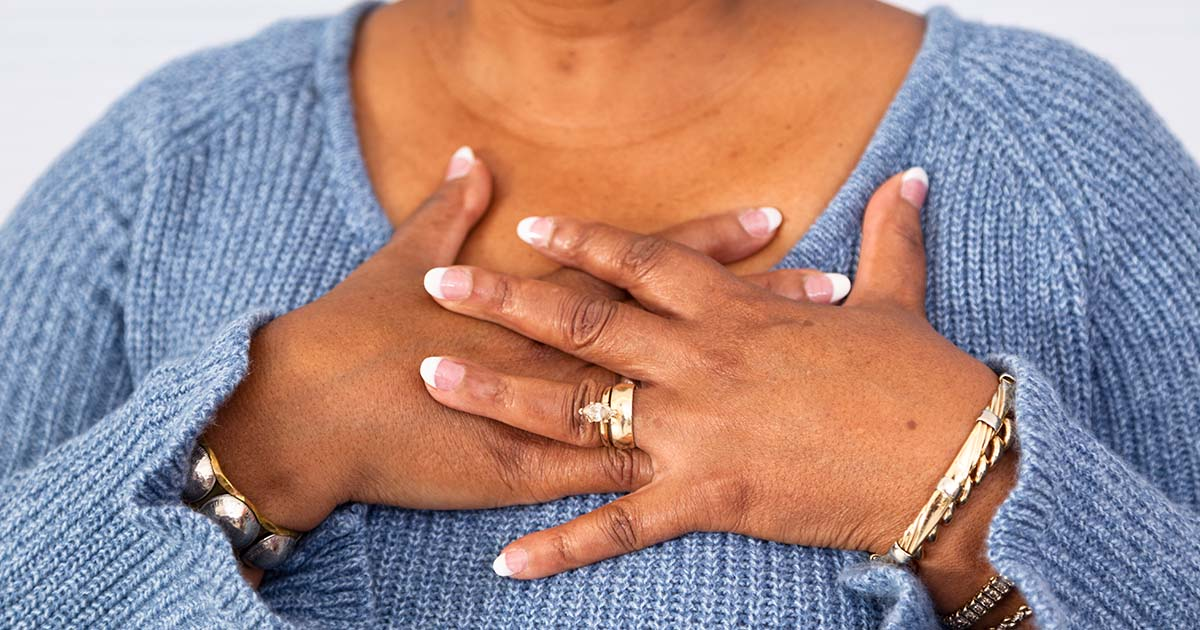 Woman has both her hands placed on top of her chest area