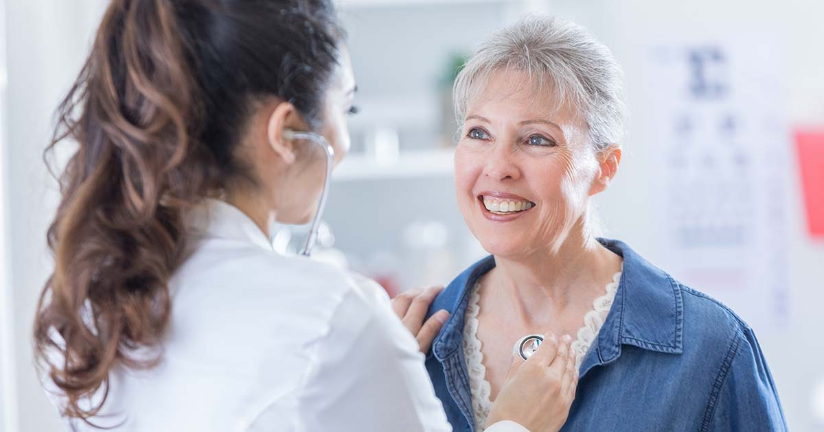 Smiling patient is listening to her doctor