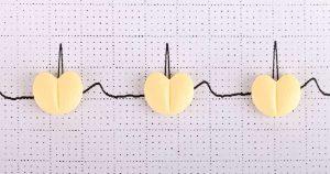 A heart rhythm line with pills on it.