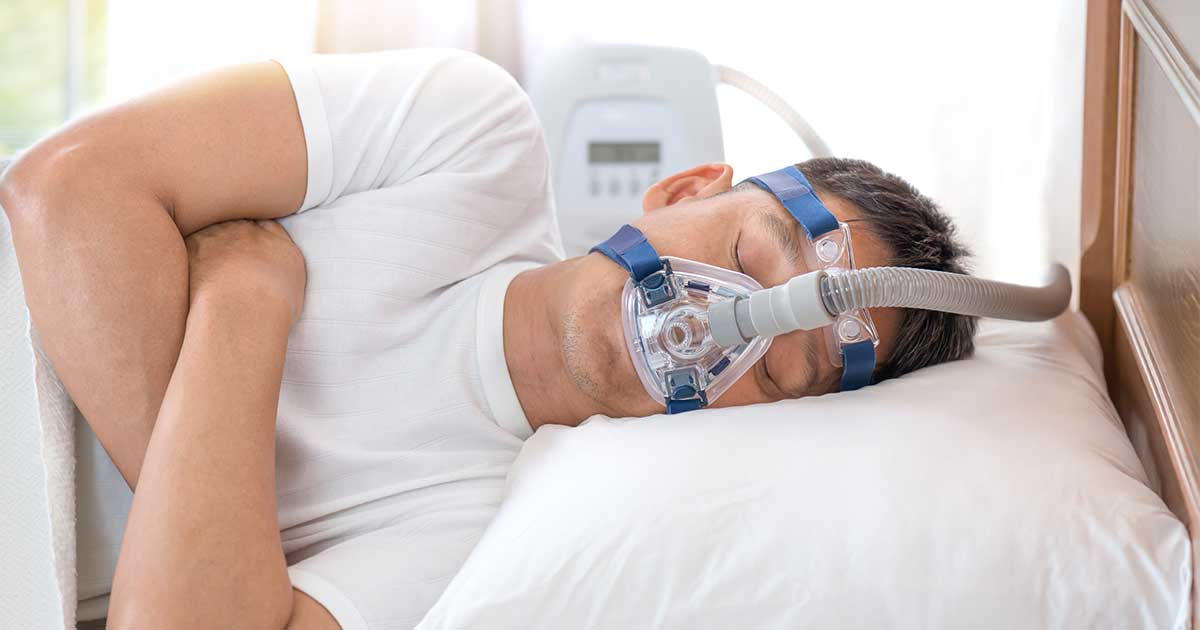 A person laying in bed wearing a CPAP machine.
